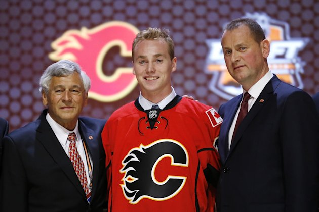 Samuel Bennett stands with Calgary Flames officials after being chosen fourth overall during the first round of the NHL hockey draft, Friday, June 27,...