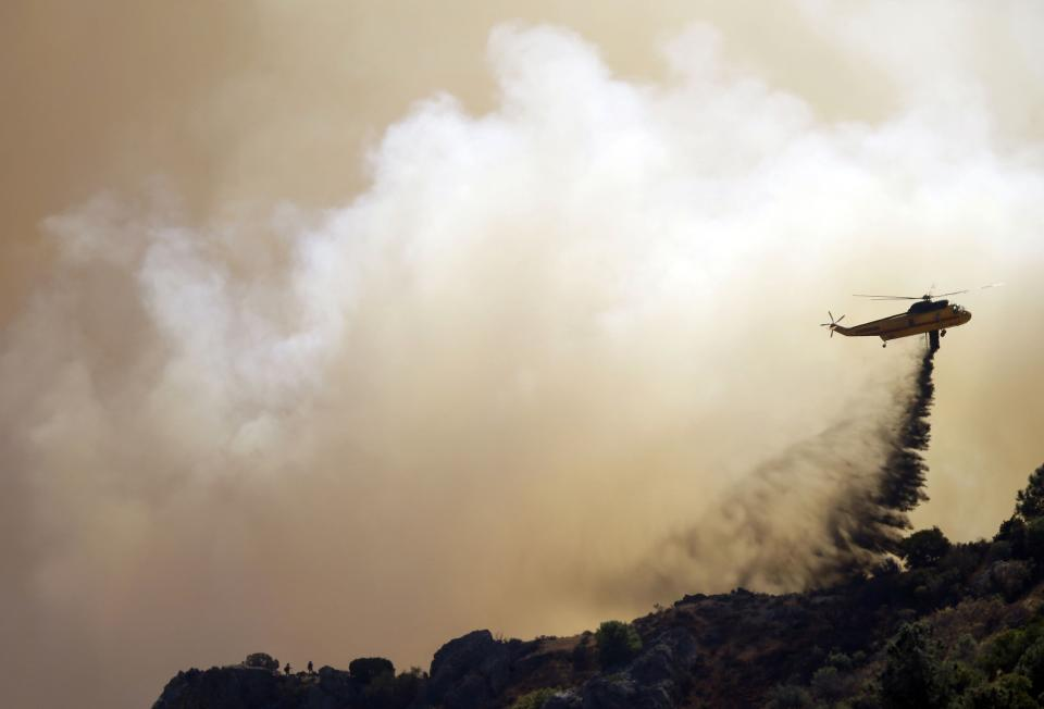 A helicopter drops retardant on a raging wildfire in Mount Diablo State Park in Contra Costa County, Calif. on Monday, Sept. 9, 2013. A wildfire burning outside Mount Diablo State Park has forced dozens of residents and animals to evacuate Monday. (AP Photo/Marcio Jose Sanchez)