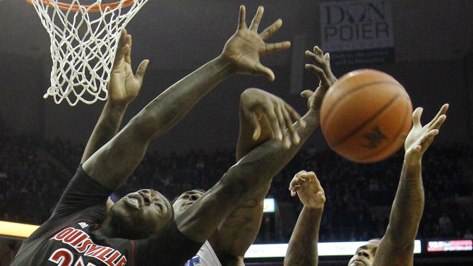 Memphis forward Tarik Black (10) bats a rebound away from Louisville players Montrezl Harrell (24) and Chane Behanan (21) during the first half of an NCAA college basketball game on Saturday, Dec. 15, 2012, in Memphis, Tenn. (AP Photo/Lance Murphey)