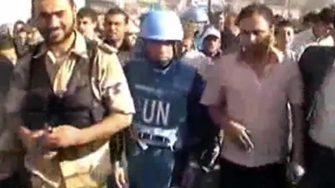 This image made from amateur video released by Shaam News Network and accessed Friday, April 27, 2012 purports to show the head of the U.N. observer team, Col. Ahmed Himmiche, center, walking in Daraa, Syria. On Friday, activists reported that thousands of people protested in the northern city of Aleppo, the central region of Hama and the northern province of Idlib. An amateur video posted online Thursday showed people carrying the body of a boy said to have been shot dead by Syrian troops in the southern city of Daraa _ apparently an attempt to display the body to U.N. monitors nearby. (AP Photo/Shaam News Network via AP video) TV OUT, THE ASSOCIATED PRESS CANNOT INDEPENDENTLY VERIFY THE CONTENT, DATE, LOCATION OR AUTHENTICITY OF THIS MATERIAL