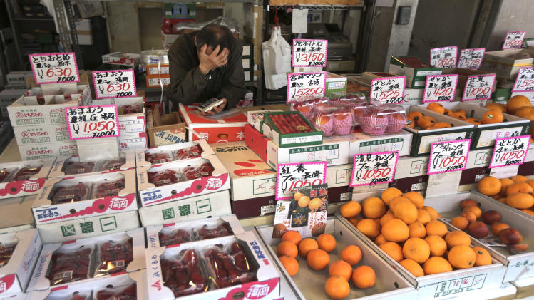 FILE - In this March 28, 2014 file photo, a fruits shop clerk waits for customers at Tsukiji fish market in Tokyo. Japan's consumer prices rose 3.2 percent from a year earlier in April to the highest level since 1991, the government said Friday, May 30, 2014, largely due to a sales tax increase.(AP Photo/Eugene Hoshiko, File)