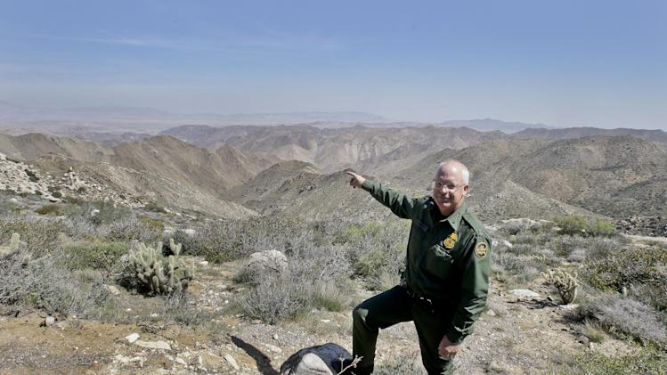 "In this Monday, March 25, 2013 photo, Border Patrol agent Richard Gordon, a 23-year veteran of the agency, points to a route used by illegal immigrants that runs through rugged mountainous terrain in the Boulevard area east of San Diego, in Boulevard, Calif. For the past 16 years, Gordon has been one of the top ""sign-cutters"" or trackers in the Border Patrol. (AP Photo/Lenny Ignelzi)"