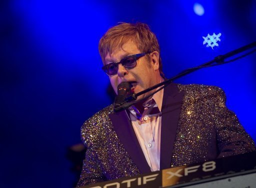 Thousands of Britons cheer as Elton John takes the stage on Ibiza, in a glittery purple jacket under a Spanish sunset