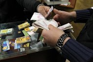 An Iranian trader exchanges a gold coin for cash in Tehran in January 2012. Young Tehranis' struggle to stay in Iran's middle class is becoming increasingly more difficult because of the country's economic straits made much worse by EU and US sanctions