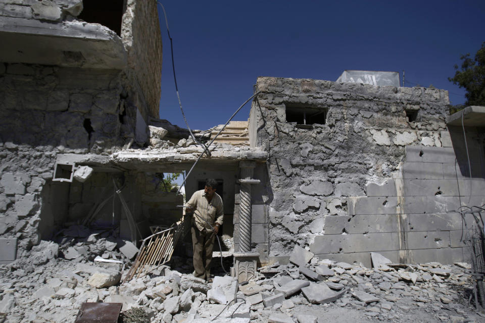 A Syrian man, walks in the rubble of a house destroyed on Wednesday, Sept. 12, 2012 from a government airstrike, in Marea, on the outskirts of Aleppo, Syria, Thursday, Sept. 13, 2012. Four people were killed in the airstrike. (AP Photo/Muhammed Muheisen)