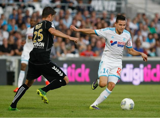 Marseille's midfielder Florian Thauvin, right, dribbles past Stade de Reims' defender Anthony Weber, to score against Reims, during their League One soccer match, at the Velodrome Stadium, in Marseill