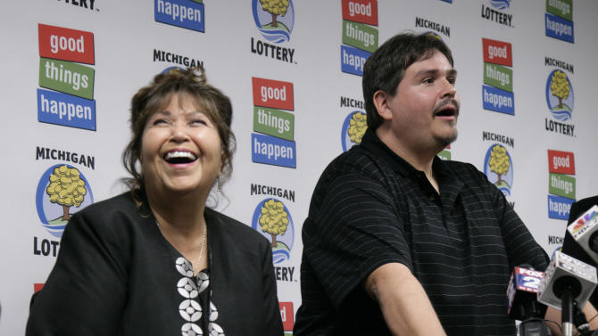 Donald Lawson, a 44-year-old Lapeer, Mich. resident, talks at a news conference in which he claimed the $337 million Powerball prize as his mother, left, laughs, Friday, Aug. 31, 2012, at the Michigan Lottery headquarters in Lansing, Mich. According to lottery officials, Lawson's mother asked to remain anonymous. Lawson elected the lump sum option of $224.6 million before state and federal taxes. (AP Photo/Al Goldis)