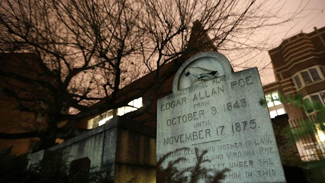In this Jan. 15, 2013 photo, a gravestone marking Edgar Allan Poe's original grave stands in a cemetery outside Westminster Hall in Baltimore. For decades, a mysterious man known as the Poe Toaster left three roses and an unfinished bottle of cognac at Poe's grave every year on the legendary writer's birthday. His identity is a great modern mystery, and just as mysteriously, the tradition ended four years ago. (AP Photo/Patrick Semansky)