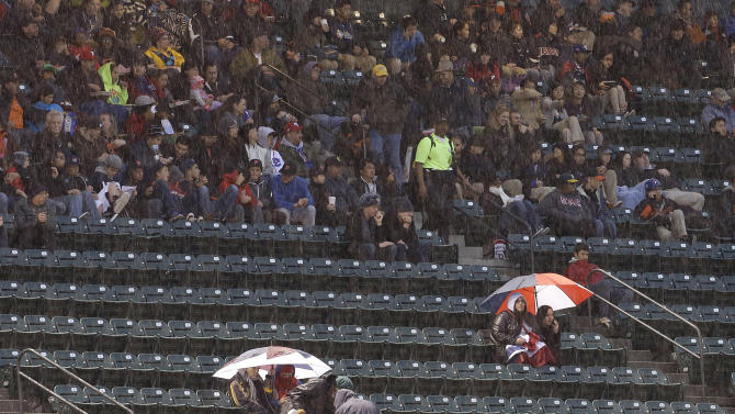 Fans watch as it rains during the fifth inning of the championship game of the World Baseball Classic between Puerto Rico and the Dominican Republic in San Francisco, Tuesday, March 19, 2013. (AP Photo/Jeff Chiu)