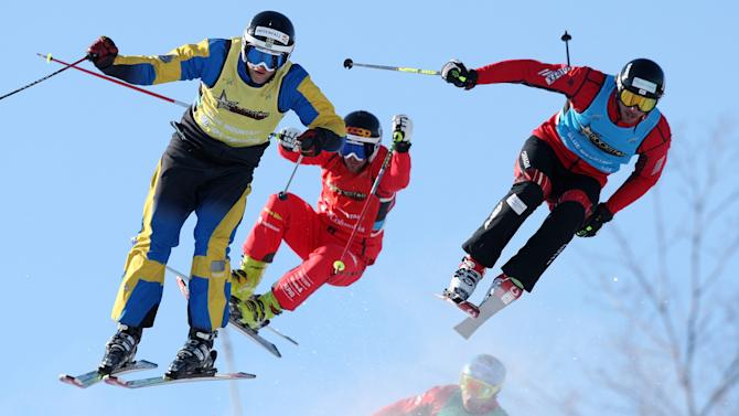 Michael Forslund of Sweden, left, Armin Neiderer of Swizerland, centre, Nick Zoricic of Canada, right, and Davey Barr of Canada, behind, fly off a jump in the Rockstar Ski Cross Grand Prix races at Blue Mountain in Collingwood, Ontario, Canada on Friday, Feb. 11, 2011. (AP Photo/The Canadian Press, Dave Chidley)