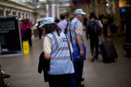 "Volunteer pastors Douglas and Magarita Barr-Hamilton roam the St. Pancras station as they look for people to help on Wednesday, Aug. 8, 2012, in London. Roaming London's transport network in blue baseball caps are 300 volunteer ""games pastors"" from a range of Christian denominations. Deployed at airports and train stations, they are ready to step into the most trivial or most serious situation, from a lost contact lens to a potential suicide. (AP Photo/Emilio Morenatti)"