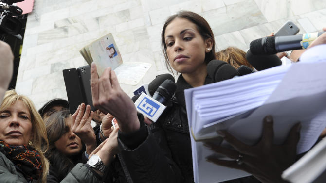 Karima el-Mahroug, also known as Ruby, bottom left, a Moroccan woman at the center of ex-Premier Silvio Berlusconi's sex-for-hire trial, holds up her passport in one hand and a stack of papers in the other as she is mobbed by reporters outside Milan's court house, Italy, Thursday, April 4, 2013. The Moroccan woman at the center of ex-Premier Silvio Berlusconi's sex-for-hire trial has denounced what she says is psychological warfare being waged against her by Italian prosecutors. Ruby, read out a lengthy statement Thursday to a gaggle of reporters in front of Milan's courthouse denying she was a prostitute and insisting that prosecutors hear her side of the story. (AP Photo/Str)