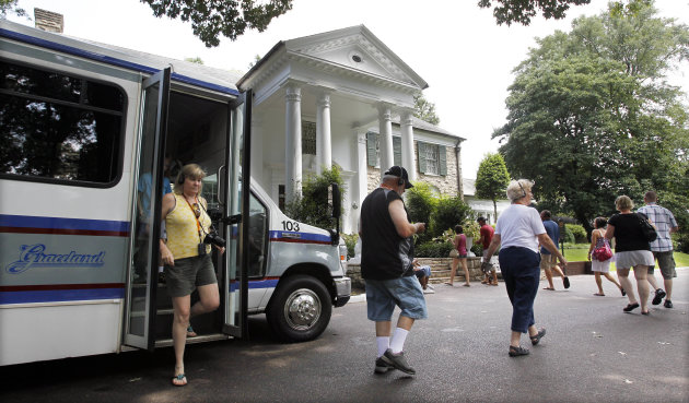 FILE -- This Aug. 2010 photo shows tourists arriving at Graceland, Elvis Presley's home in Memphis, Tenn. Graceland opened for tours on June 7, 1982. They sold out all 3,024 tickets on the first day and didn't look back, forever changing the Memphis tourist landscape while keeping Elvis and his legend alive.(AP Photo/Mark Humphrey)