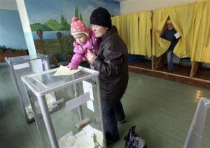A child holds the ballot of his mother during the referendum …