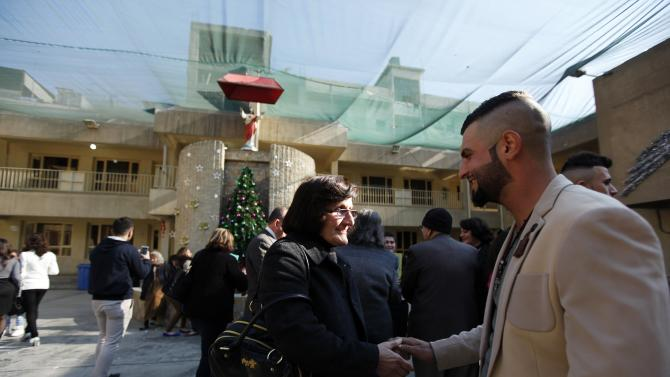 Iraqi Christians exchange greetings after a mass at Sacred Heart Catholic Church in Baghdad