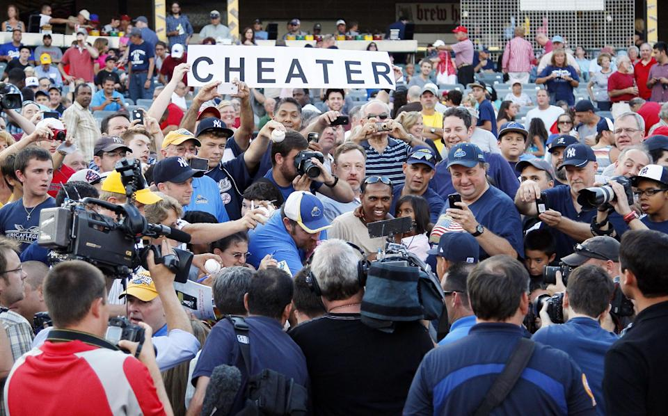 "A fan holds a sign that reads ""CHEATER,"" as New York Yankees' Alex Rodriguez is surrounded by members of the media while singing autographs before the start of a Class AA baseball game with the Trenton Thunder against the Reading Phillies, Friday, Aug. 2, 2013, in Trenton, N.J. (AP Photo/Tom Mihalek)"