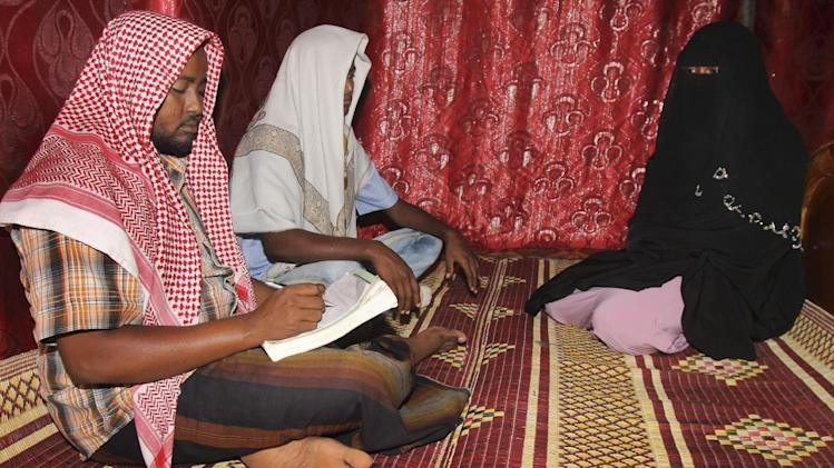 In this photo taken Wednesday, March 13, 2013, Abdi Ali, 25, center-left, and his girlfriend Anisa, 23, right, sit with an Islamic cleric, left, who marries eloping couples, during their elopement marriage in Walaweyn, Somalia. Since the Islamic extremist rebels of al-Shabab have been pushed out of almost all of Somalia's cities and towns, life has begun to return to normal - including elopements which al-Shabab under its strict interpretation of Islamic Shariah law had declared illegal and punishable by whipping or even death by stoning. (AP Photo/Farah Abdi Warsameh)