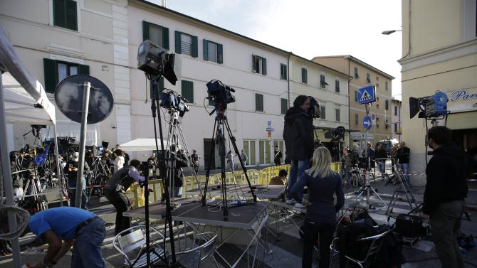 Journalist prepare their equipment in front of the Teatro Moderno theater where the first hearing of the trial for the Jan. 13, 2012 tragedy, where 32 people died after the luxury cruise Costa Concordia was forced to evacuate some 4,200 passengers after it hit a rock while passing too close to the Giglio Island, is taking place, in Grosseto, Italy, Monday Oct. 15, 2012. (AP Photo/Gregorio Borgia)
