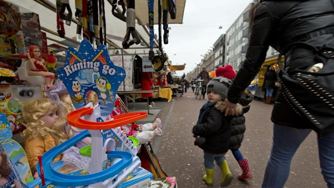 This March 20, 2013 photo shows a mother urging her children away from toys in a stand at Albert Cuyp market, Amsterdam, Netherlands. Amsterdam's wealth began in its port with the merchants who bought and sold everything from tulip bulbs to spices from the East Indies. A little of that mercantile past can still be seen at the city's many markets. The most famous is the Albert Cuyp food market in the Pijp neighborhood, which sells, as the city website puts it, everything from cheese to bicycle chains, six days a week. (AP Photo/Peter Dejong)
