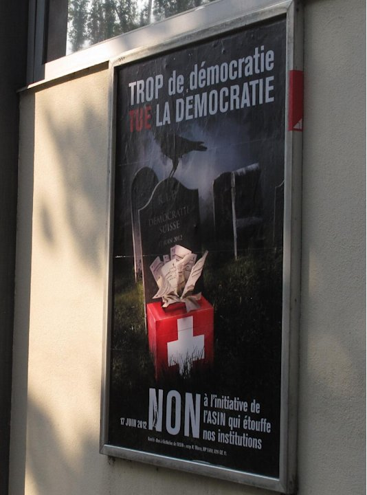 FILE - In this picture taken May 24, 2012 a  poster, right, seen in Geneva, Switzerland,  urging Swiss voters to reject a proposal to automatically hold a referendum whenever the government signs an i