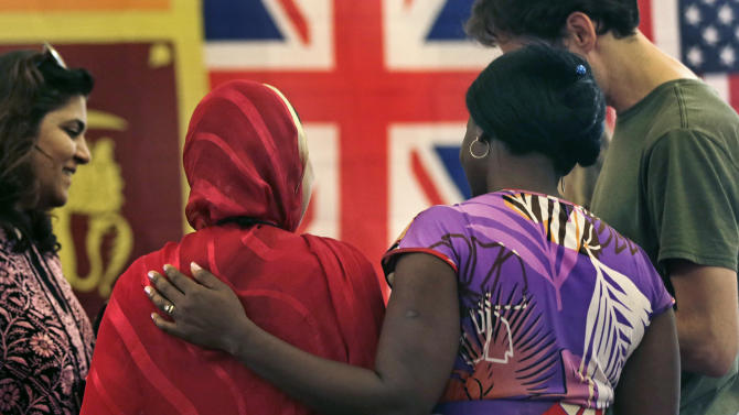 """Rosemary Shav, a chaperone from Nigeria, right, puts her arm on the back of Nafeesa Rahman Qazi, of Northern Pakistan, while attending the """"Common Bond"""" summer camp in Newbury, Mass., Wednesday, July 18, 2012.  Teens from across the world who lost loved one due to terrorism gathered for the 10 day camp to share their feelings, insights and a chance to be the world's next generation of international peacemakers. Qazi, who is a community activist and works in a children's clinic in her homelnad, lost two cousins to the Taliban. (AP Photo/Charles Krupa)"""