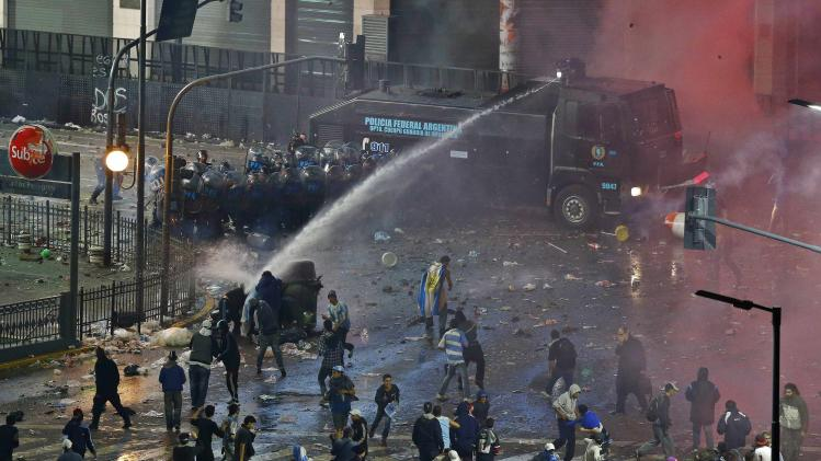 Argentina's fans clash with riot police after Argentina lost to Germany in their 2014 World Cup final soccer match in Brazil, at a public square viewing area in Buenos Aires