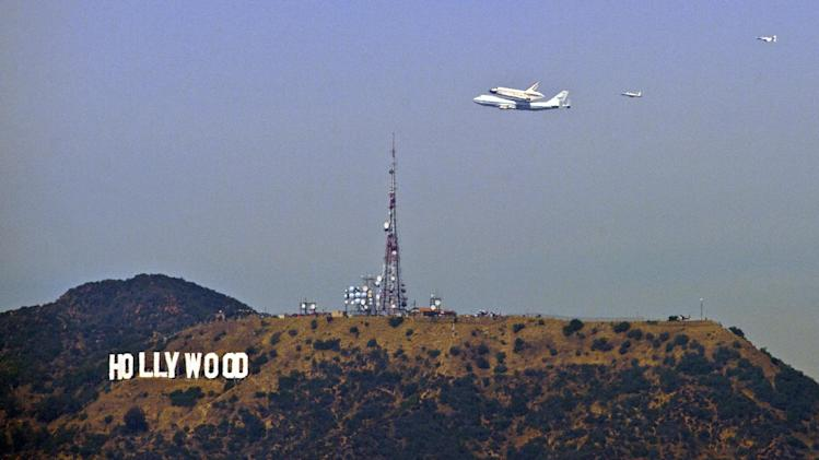 The Space Shuttle Endeavour atop a modified 747 passes the Hollywood Sign as seen from Dodger Stadium, Friday, Sept. 21, 2012, in Los Angeles, the last aerial hurrah before retiring to a Los Angeles museum. (AP Photo/Mark J. Terrill)