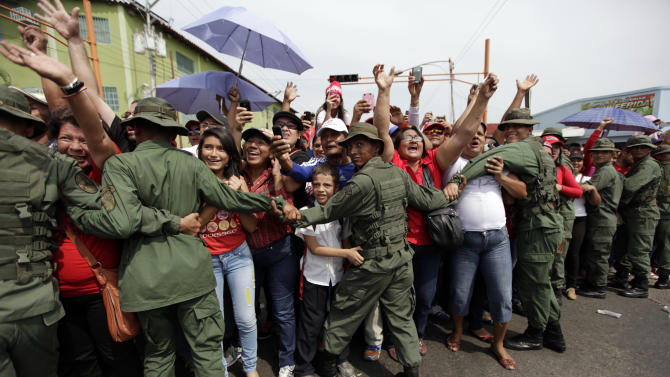 Supporters of Venezuela's interim President Nicolas Maduro greet him upon his arrival to a campaign rally in Barinas, Venezuela, Tuesday, April 2, 2013. Late President Hugo Chavez's chosen successor, Nicolas Maduro is competing against opposition leader Henrique Capriles in the April 14 presidential election. (AP Photo/Ariana Cubillos)
