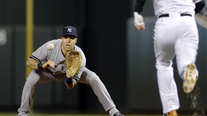 A throw to New York Yankees first baseman Mark Teixeira, left, beats Baltimore Orioles' Jonathan Schoop in the third inning of a baseball game, Sunday, Sept. 14, 2014, in Baltimore. (AP Photo/Patrick Semansky)