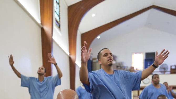In this photo taken Thursday, Aug. 9, 2012 inmate William Johnson, 38, foreground, attends a college-level seminary course held at the California Rehabilitative Center in Norco, Calif. The program, called The Urban Ministry Institute, TUMI, started as an experiment in Norco's prison four years ago and is now expanding to 18 California prisons and nearly 900 inmates, including women, thanks to a $2.1 million gift from a wealthy Malibu real estate entrepreneur. The nonprofit group Prison Fellowship, which trains volunteers and runs the rigorous, three-year course behind prison walls, graduated its first class of 10 inmates last year and expects to graduate 14 more in 2013. It has also helped prisons in Michigan, Florida and Colorado start classes. (AP Photo/Damian Dovarganes)