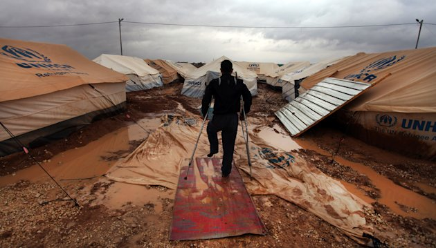 A Wounded Syrian refugee man makes his way on water and mud, at Zaatari Syrian refugee camp, near the Syrian border in Mafraq, Jordan, Tuesday, Jan. 8, 2013. Syrian refugees in a Jordanian camp attack