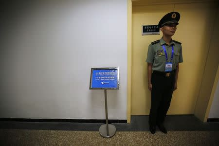 A soldier of the PLA stands in front of a laboratory of angel electronic techniques during an organised media tour at a PLA engineering academy in Beijing