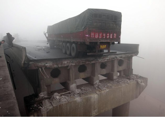 In this photo provided by China's Xinhua News Agency, a truck sits on the expressway bridge which partially collapsed due to an explosion in Mianchi County, Sanmenxia, central China's Henan Province, 