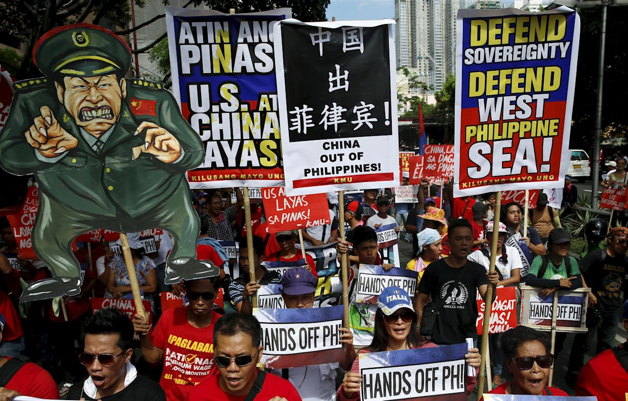 Activists display signs and a placard of a Chinese soldier as they march towards the Chinese Consulate during a protest over the South China Sea disputes, in Makati City, Metro Manila