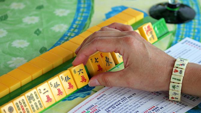 This May 31, 2013 photo shows a woman handling mahjong pieces during a game night gathering in Mayfield Village, Ohio. For the baby boomer generation, getting together to play games is a way to stay active and social. It also can help people stay mentally sharp. (AP Photo/Bonnie Gruttadauria)