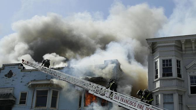 San Francisco firefighters battle a four-alarm fire at a residential and commercial building on the corner of Valencia Street and Duboce Avenue in San Francisco, Sunday, May 6, 2012. (AP Photo/Jeff Chiu)
