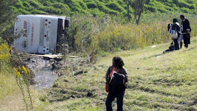 Passengers look on after their bus overturned in a ditch at an exit ramp off Route 80 in Wayne, N.J. Saturday, Oct. 6, 2012. The chartered tour bus from Toronto carrying about 60 people overturned on an interstate exit ramp. Three people have been taken to hospital with non-life-threatening injuries. (AP Photo/Bill Kostroun)