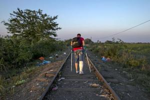 A migrant, hoping to cross into Hungary, walks along…