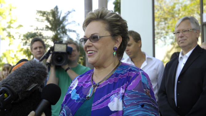 Lindy Chamberlain-Creighton speaks to the media as her ex-husband, Michael Chamberlain, right, listens outside a coroner's court in Darwin, Australia, Tuesday, June 12, 2012. Settling a notorious 1980 case that split the nation and led to a mistaken conviction, an Australian coroner ruled that a dingo took a baby from a campsite in the Outback, just as her mother said from the beginning. (AP Photo/AAP, Patrina Malone) AUSTRALIA OUT, NO SALES, NO ARCHIVES