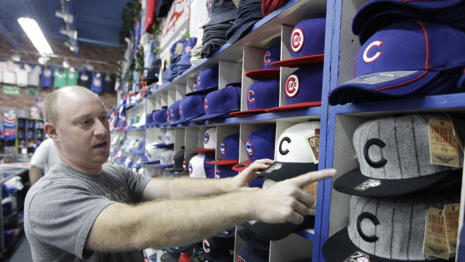 Brad Rosen points to the Chicago Cubs' home, left, and away, right, ball caps from the team's last world championship season in 1908, at Sports World near Wrigley Field, Thursday, Sept. 27, 2012, in Chicago. Even for a team with a record of futility unmatched in professional baseball and, heck, all of professional sports, this season has been one of the most dismal in Cubs history. About the only good thing that could be said about a team poised to lose 100 games for the first time in 46 years--one of which came after the shortstop trotted off the field thinking there were three outs instead of two--is that it is doing so in front of fewer fans than any year in the last decade. (AP Photo/M. Spencer Green)