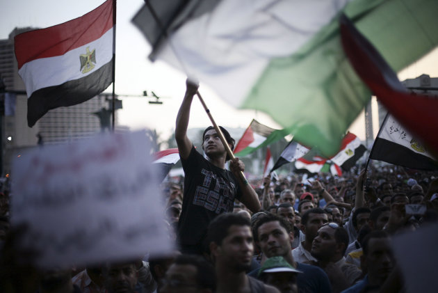 Egyptian protesters wave national flags and banners in Tahrir Square in Cairo, Egypt, Thursday, 21 June, 2012. Authorities delayed Thursday's planned announcement of the winner of Egypt's presidential