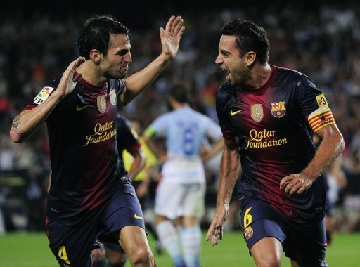 Barcelona&#39;s Xavi Hernandez (R) is congratuled by his teamate Cesc Fabregas after scoring during their Spanish La Liga match against Granada at the Camp Nou stadium in Barcelona. Barcelona won 2-0