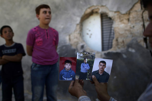 Syrian Hamzah Abu Bakri, Displays portraits of his brothers, from right, Bakri, Mohammed and Abdul Baset, who were killed on Thursday from government forces shelling while standing by their vegetables
