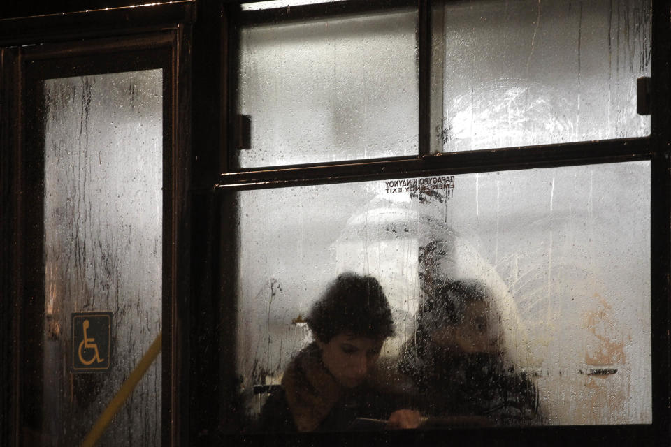 Passengers are seen through a window of a bus during a heavy rainfall  in central Athens on Monday, Feb. 6, 2012. Authorities in northeastern Greece announced the voluntary evacuation of people in flood-stricken villages on the Turkish border. (AP Photo / Petros Giannakouris)