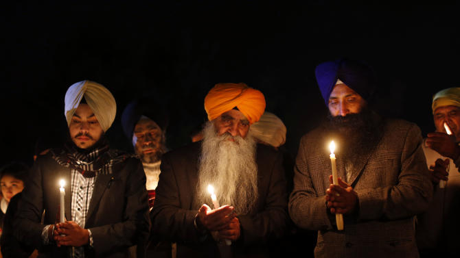 Members of the Sikh community hold a candlelight vigil outside Newtown High School before an interfaith vigil with President Barack Obama, Sunday, Dec. 16, 2012, in Newtown, Conn.  A gunman walked into Sandy Hook Elementary School in Newtown Friday and opened fire, killing 26 people, including 20 children. (AP Photo/Jason DeCrow)