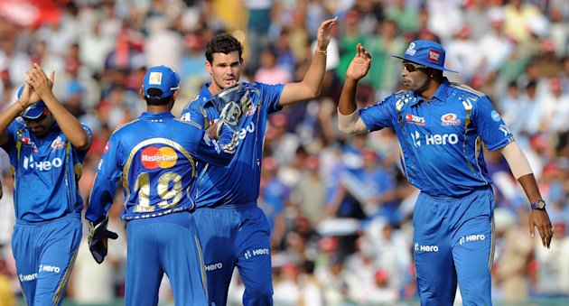 Mumbai Indians bowlwr Clint McKay (2R) celebrates the wicket of Kings XI Punjab batsman Nitin Saini with teammates during the IPL Twenty20 cricket match between Kings XI Punjab and Mumbai Indians at P