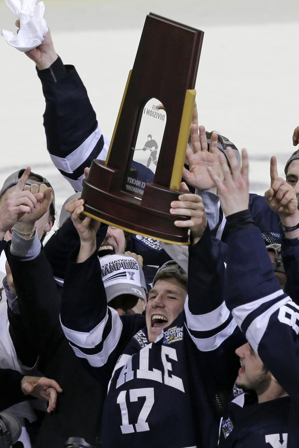 Yale captain Andrew Miller (17) hoists the trophy after Yale won  the NCAA men's college hockey national championship game over Quinnipiac 4-0, in Pittsburgh Saturday, April 13, 2013.  (AP Photo/Gene Puskar)
