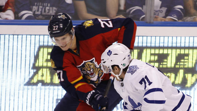 Toronto Maple Leafs right wing David Clarkson (71) and Florida Panthers center Nick Bjugstad (27) fight for the puck during the third period of an NHL hockey game Sunday, Dec. 28, 2014, in Sunrise, Fla. Florida defeated Toronto 6-4. (AP Photo/Terry Renna)