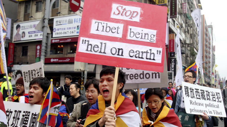 Tibetans living in Taiwan and supporters shout slogans during a protest to mark the March 10 anniversary of a failed 1959 uprising against Chinese rule, in Taipei, Taiwan, Sunday, March 9, 2014. (AP Photo/Chiang Ying-ying)