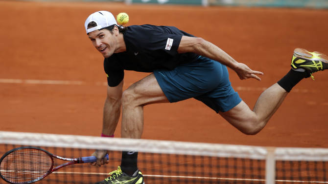 Germany's Tommy Hass returns the ball to Russia's Mikhail Youzhny during their fourth round match of the French Open tennis tournament at the Roland Garros stadium Monday, June 3, 2013 in Paris. Haas won 6-1, 6-1, 6-3. (AP Photo/Christophe Ena)